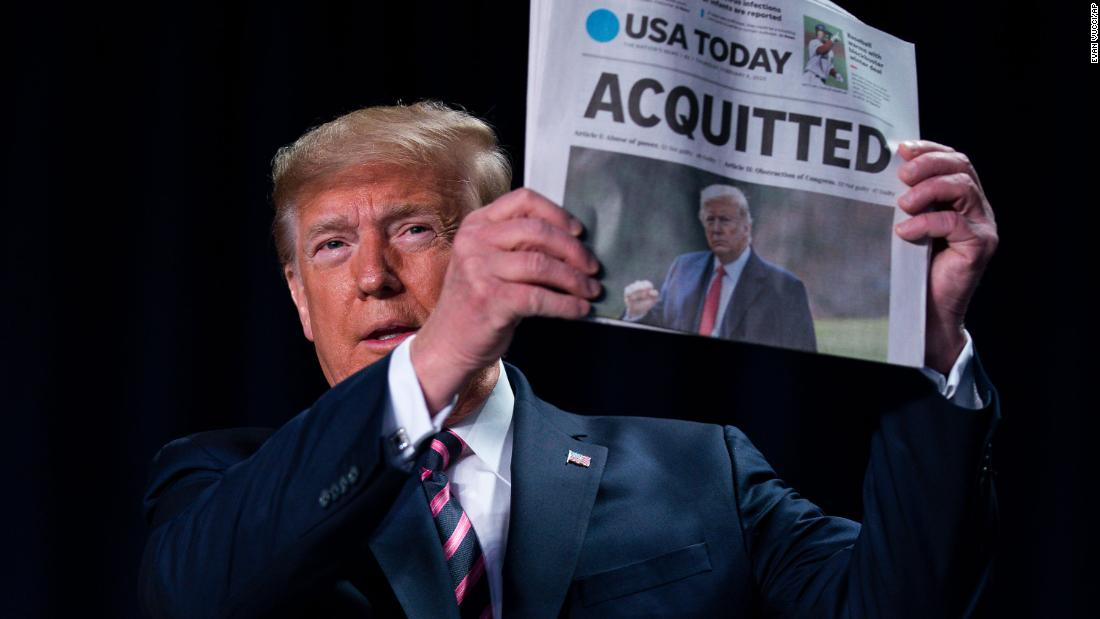 President Donald Trump holds up a newspaper at the 68th annual National Prayer Breakfast in Washington on February 6.